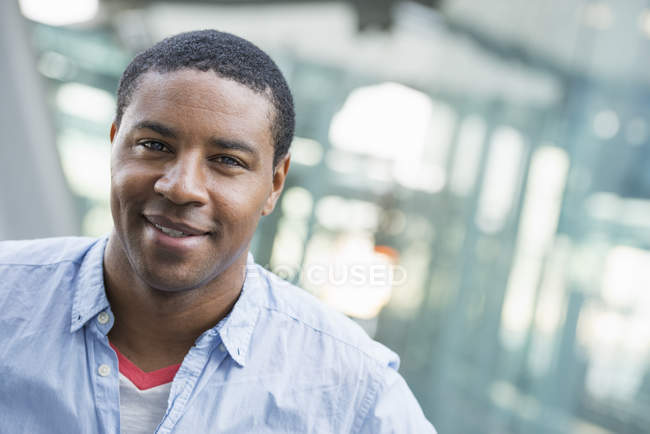 African american man in blue shirt standing in front of modern building. — Stock Photo