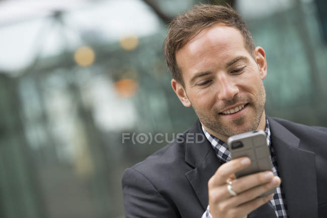 Homme aux cheveux courts roux et barbe en costume en utilisant un smartphone en ville . — Photo de stock