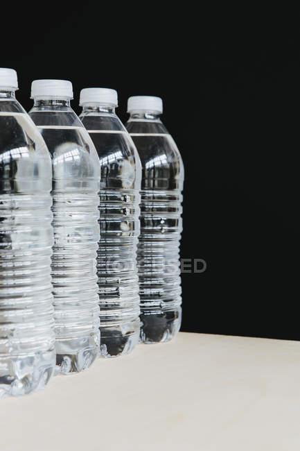 Fila de garrafas de água de plástico transparente cheias de água filtrada . — Fotografia de Stock