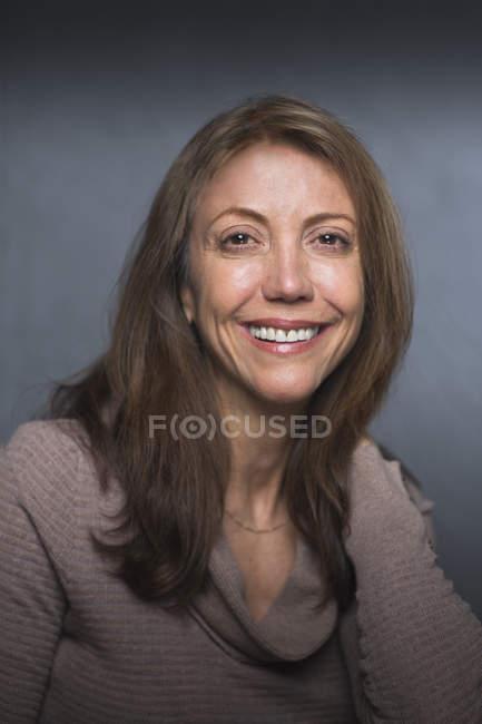 Портрет улыбающейся женщины средних лет на сером фоне . — стоковое фото