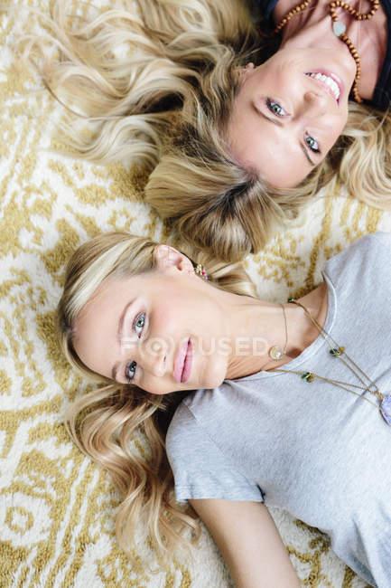 Due donne che si trovano sul tappeto e guardando a porte chiuse. — Foto stock