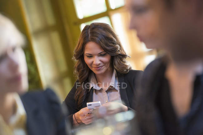 Young woman sitting at bar table and using smartphone with people in foreground. — Stock Photo