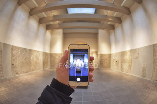 Close-up of male hand holding smartphone and taking picture of large room. — Stock Photo