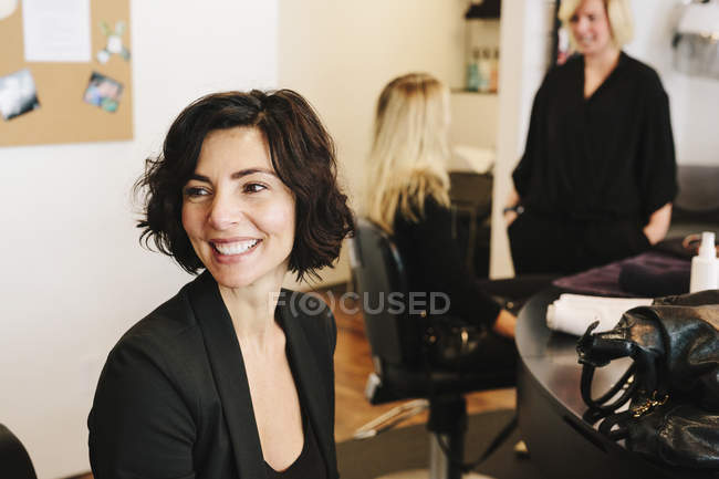 Client sitting at hair salon with people in background. — Stock Photo