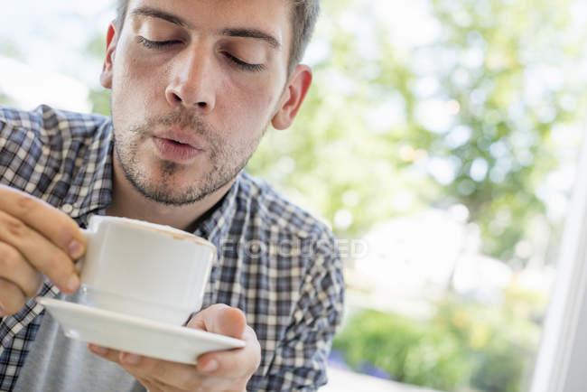 Людина, що дме на поверхні гарячої кави. — стокове фото