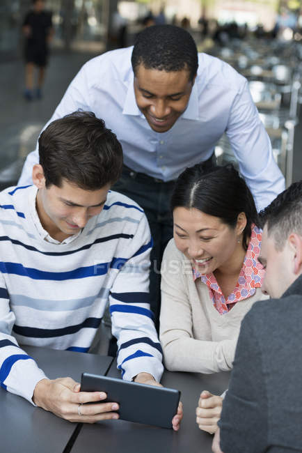 Four people gathered around table in city and sharing digital tablet together. — Stock Photo
