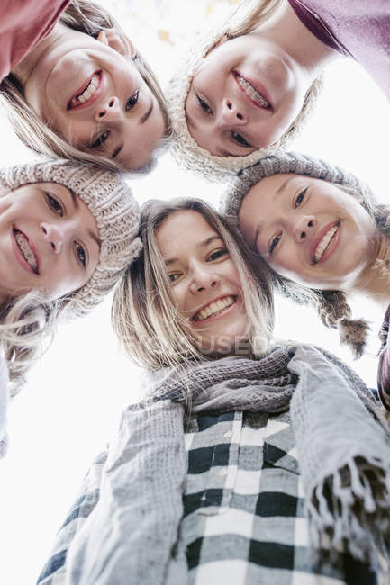 Five teenage girls in woolly hats and scarves looking down in camera outdoors. — Stock Photo