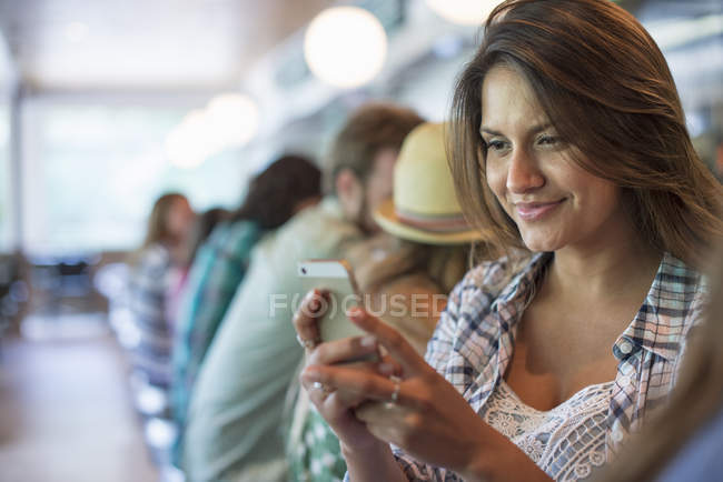 Woman looking at smartphone with row of customers in diner cafe. — Stock Photo