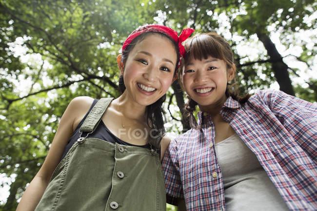 Низкий угол обзора молодых женщин, смотрящих в камеру в лесу . — стоковое фото