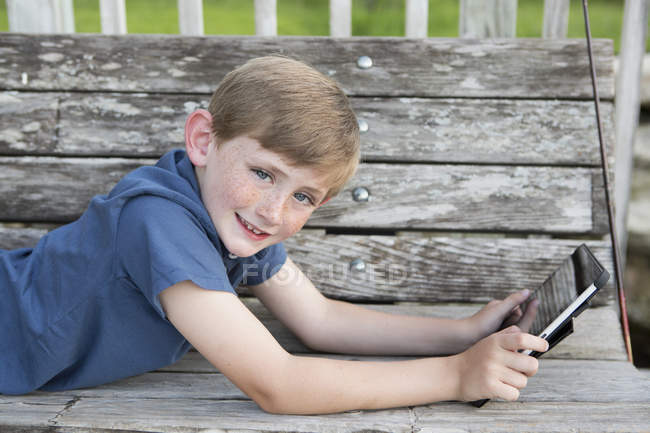 Elementary age boy lying on front at wooden bench outdoors with digital tablet. — Stock Photo