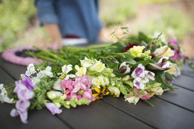 Sommerblumenstrauß auf Gartentisch mit Person im Hintergrund. — Stockfoto