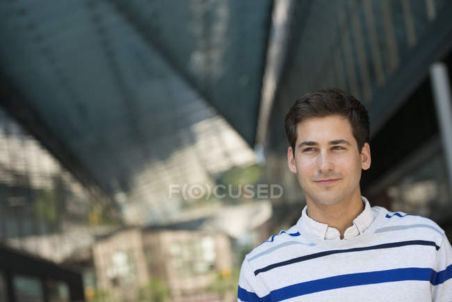 Portrait of young man in striped sweater looking into distance. — Stock Photo