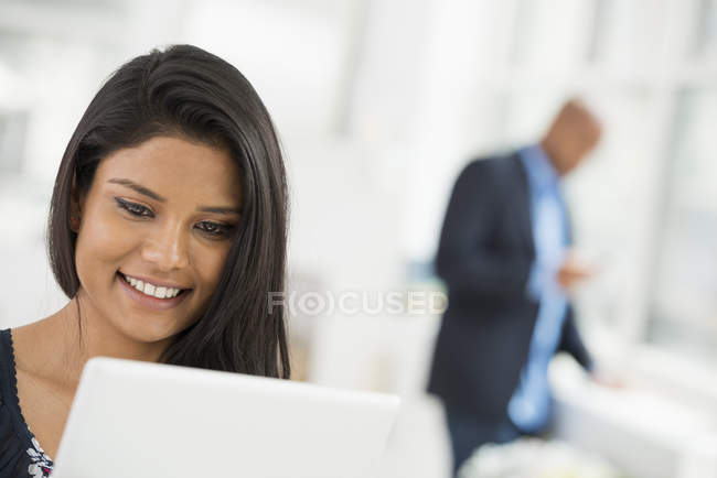 Close-up of young woman using digital tablet in office workplace. — Stock Photo