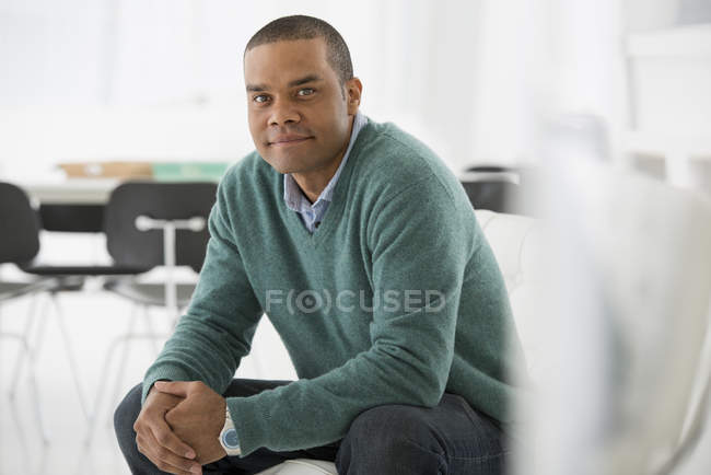 Mid adult man sitting with hands clasped in relaxed confident pose in office. — Stock Photo