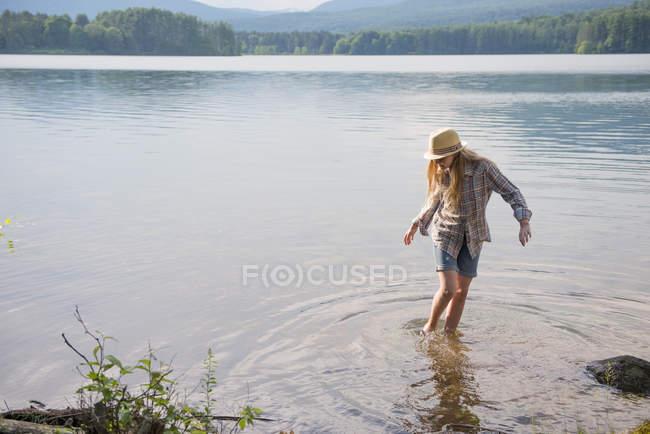 Menina adolescente no chapéu de palha a remar em águas rasas do lago do país. — Fotografia de Stock