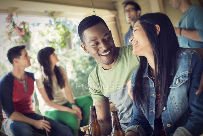 Man and woman drinking beer with fiends at house party. — Stock Photo