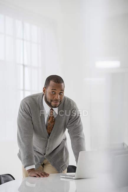Средний взрослый мужчина, склонившись над столом, используя ноутбук и глядя в камеру в офисе — стоковое фото