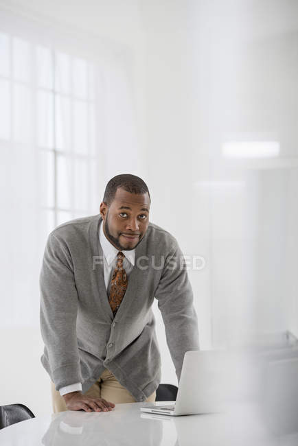 Mid adult man leaning over table, using laptop and looking in camera in office. — Stock Photo