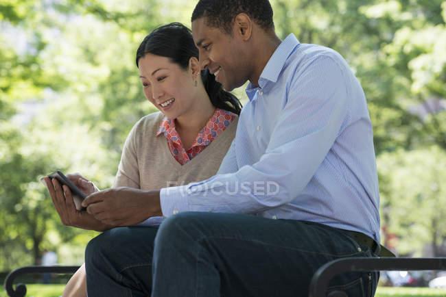 Metà adulto uomo e donna utilizzando smartphone insieme nel parco cittadino . — Foto stock