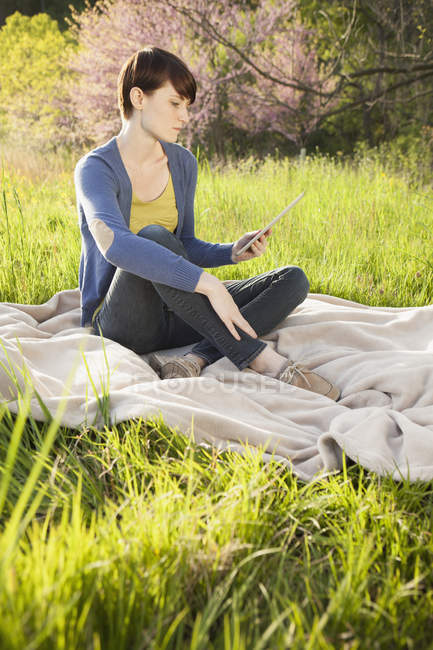 Jovem mulher sentada no campo gramado em cobertor e usando tablet digital . — Fotografia de Stock