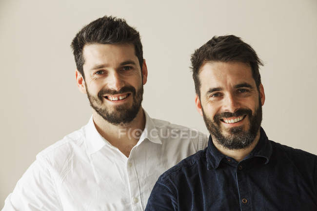 Portrait of two bearded men smiling and looking in camera. — Stock Photo