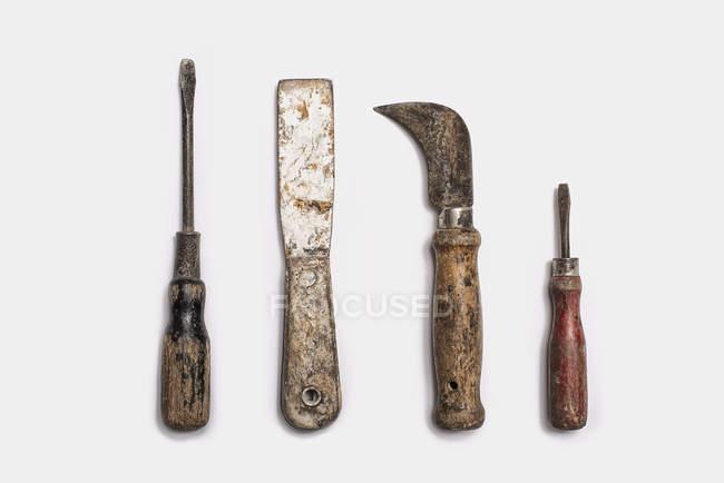 Outils bien utilisés, disposées en rang sur fond blanc. — Photo de stock