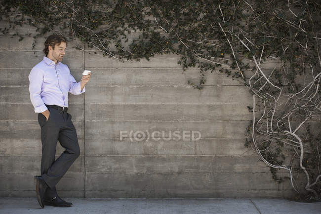 Young man leaning on wall in park and checking smartphone. — Stock Photo
