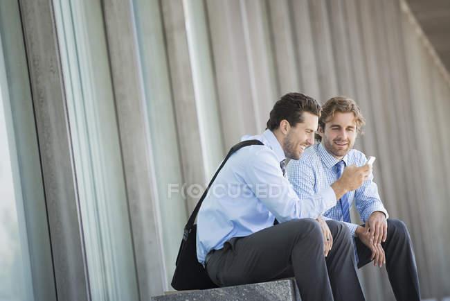 Двоє бізнесменів, які сидять за межами офісу, будівництво та перевірки смартфон. — стокове фото