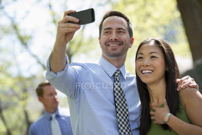 Paar nehmen Selfie mit Smartphone mit Mann im Hintergrund — Stockfoto