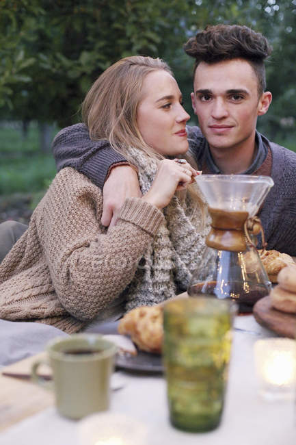 Couple embracing while sitting at outdoor table with food and drink. — Stock Photo