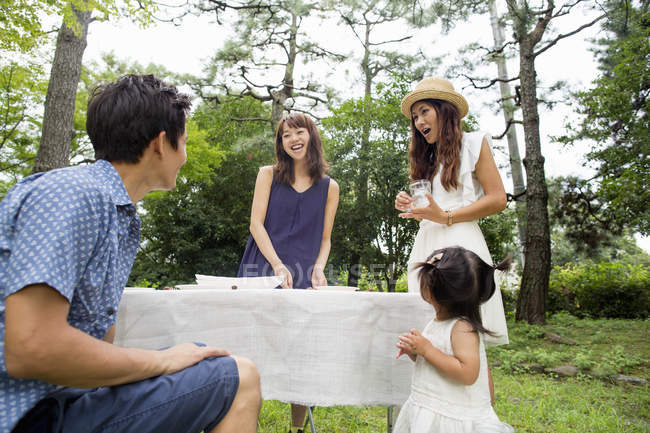 Group of Japanese friends with toddler girl serving table for outdoor party in forest. — Stock Photo