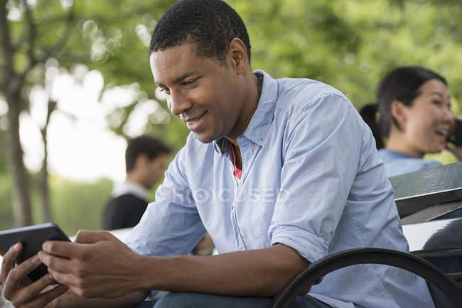 Uomo seduto sulla panchina e utilizzando tablet digitale con donna che parla al telefono in background . — Foto stock