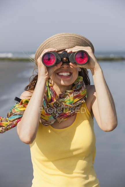 Женщина в кепку и шарф с помощью бинокля на пляже на Нью Джерси Шор, США. — стоковое фото