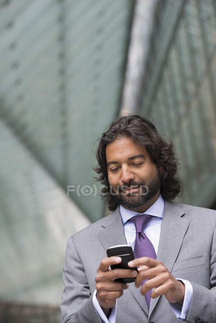 Mature man in business suit with beard and curly hair using smartphone. — Stock Photo
