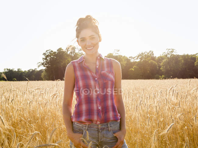 Young woman standing in field of tall corn plants in soft light and smiling. — Stock Photo