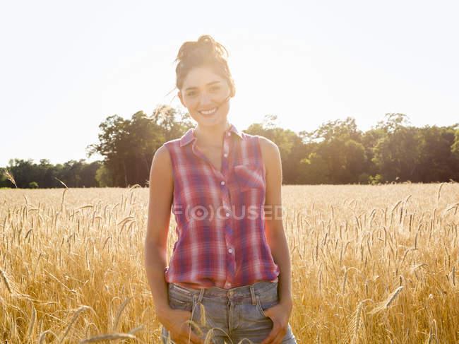 Jovem mulher em pé no campo de plantas de milho alto em luz macia e sorrindo . — Fotografia de Stock