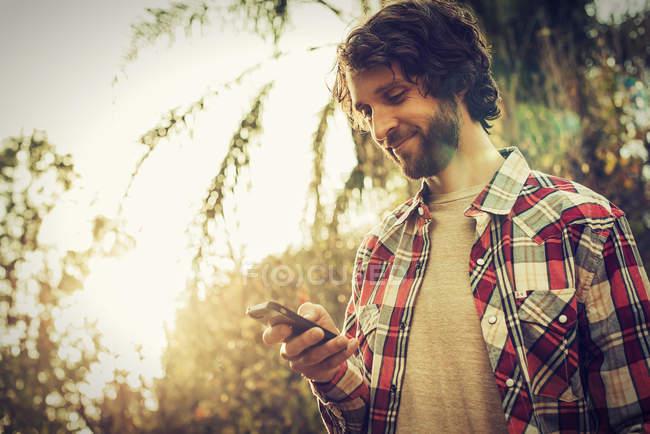 Vue à angle bas d'un homme barbu vérifiant son smartphone à l'extérieur . — Photo de stock