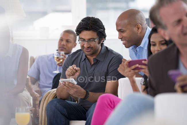 Petit groupe de personnes vérifiant les smartphones lors de réunions sociales à l'intérieur . — Photo de stock