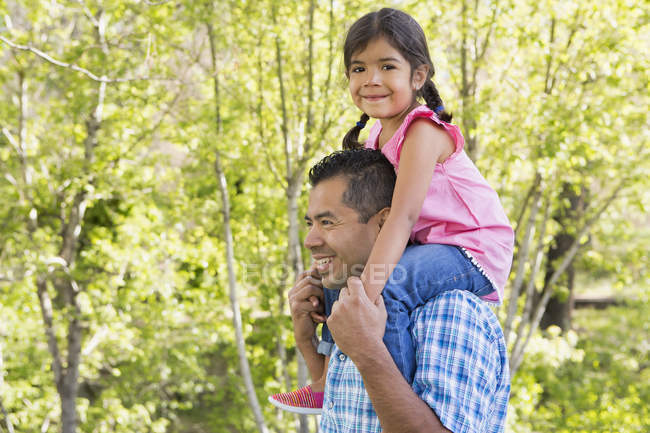 Mature homme donnant fille piggyback tour dans le parc . — Photo de stock