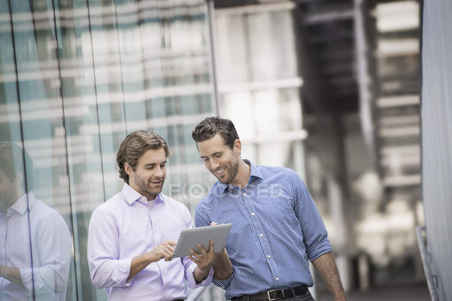 Two men standing outside building and using digital tablet together. — Stock Photo