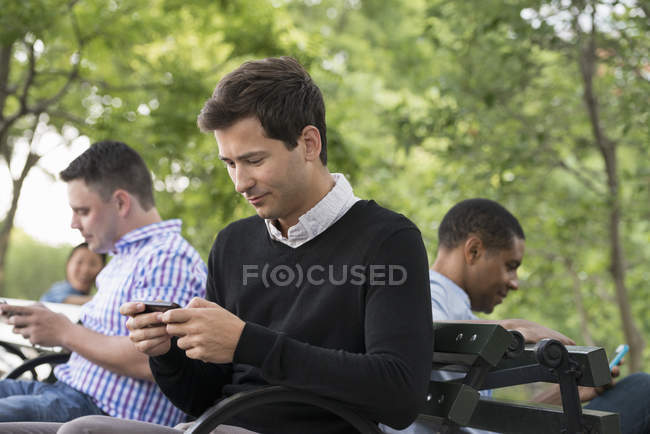 Group of people sitting in park and using smartphones on bench. — Stock Photo