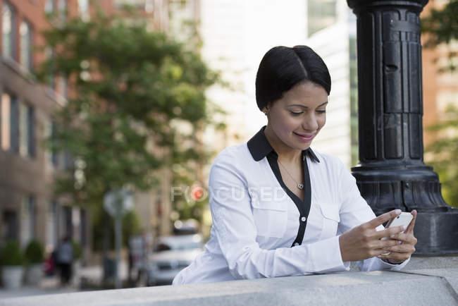 Femme adulte moyenne en veste blanche vérifier téléphone dans la rue . — Photo de stock