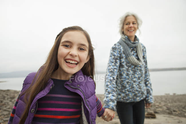 Femme d'âge mûr tenant par la main avec pré adolescente — Photo de stock