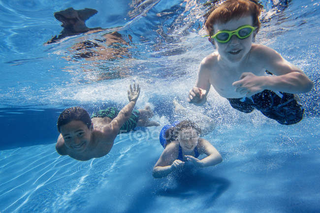Three children swimming underwater and smiling in camera. — Stock Photo