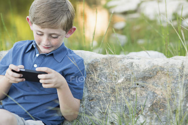 Junge im Grundschulalter lehnt an Stein und spielt mit Smartphone. — Stockfoto