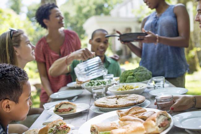 Amigos e família, reunindo em torno da mesa de jantar no jardim campestre. — Fotografia de Stock