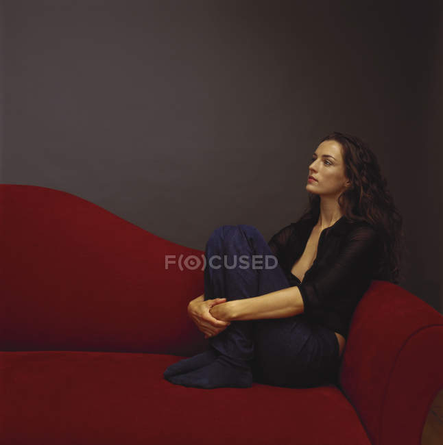 Woman in black casual clothing hugging knees and leaning on red couch. — Stock Photo