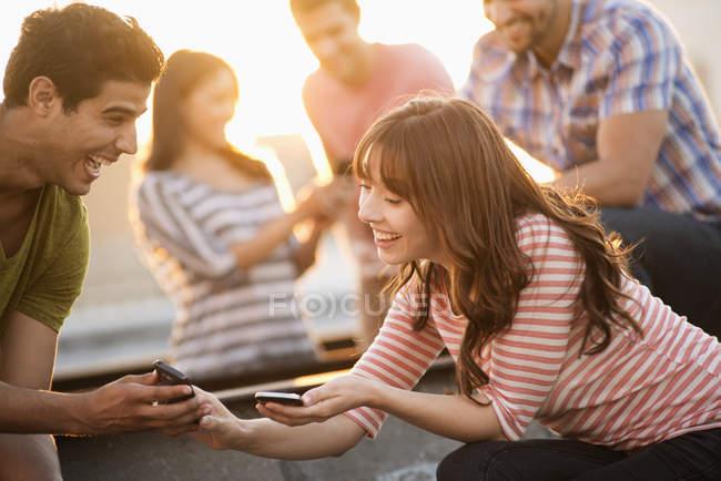 Jóvenes amigos compartiendo teléfonos inteligentes en la terraza de la azotea fiesta . - foto de stock