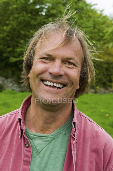 Homem em roupas casuais com cabelo loiro sorrindo ao ar livre . — Fotografia de Stock