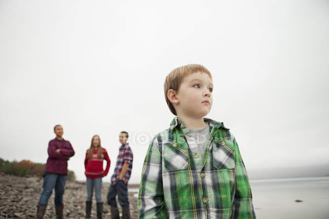 Подростки и мальчик, стоящие на берегу . — стоковое фото